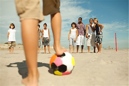 Boys playing football on beach Stock Photo - Premium Royalty-Free, Code: 6114-06600849