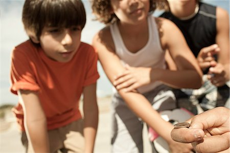 Boys tossing a coin Stock Photo - Premium Royalty-Free, Code: 6114-06600863