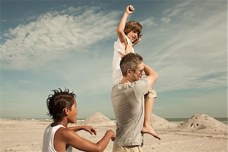 Boy being carried on shoulders Stock Photo - Premium Royalty-Free, Code: 6114-06600860
