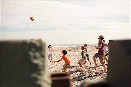 Boys playing football on beach, view through wall Stock Photo - Premium Royalty-Free, Code: 6114-06600862
