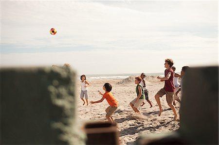 Boys playing football on beach, view through wall Stock Photo - Premium Royalty-Free, Code: 6114-06600862