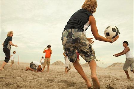 Boys playing football on beach Stock Photo - Premium Royalty-Free, Code: 6114-06600870