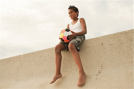Boy sitting on wall with football Stock Photo - Premium Royalty-Free, Code: 6114-06600803