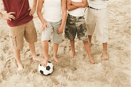Boys standing on beach with football Stock Photo - Premium Royalty-Free, Code: 6114-06600810