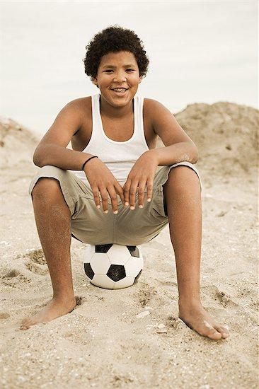 Portrait of boy sitting on top of football Stock Photo - Premium Royalty-Free, Image code: 6114-06600817