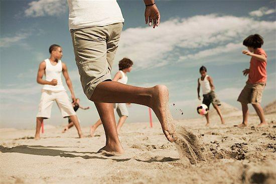 Boys playing football on beach Stock Photo - Premium Royalty-Free, Image code: 6114-06600816