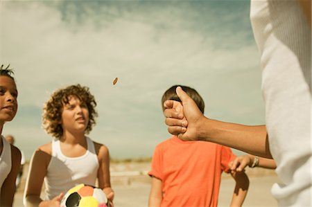Boys tossing a coin Stock Photo - Premium Royalty-Free, Code: 6114-06600826