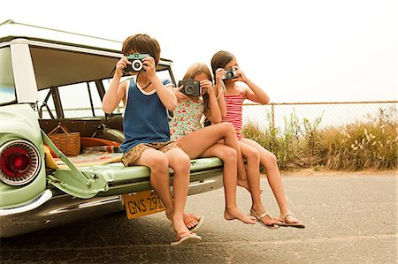 Three children sitting on back of estate car taking photographs Stock Photo - Premium Royalty-Free, Code: 6114-06600940