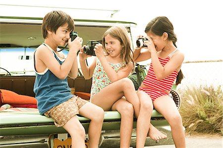 Three children sitting on back of estate car taking photographs Stock Photo - Premium Royalty-Free, Code: 6114-06600941
