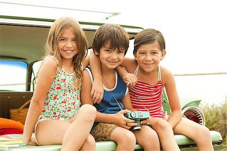 Three children sitting on back of estate car wearing swimwear Stock Photo - Premium Royalty-Free, Code: 6114-06600944