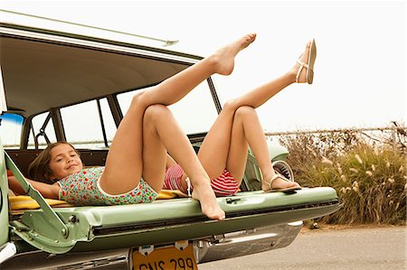 Two girls lying in estate car with legs in the air Stock Photo - Premium Royalty-Free, Code: 6114-06600948