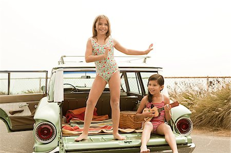 Girl dancing on car boot, another girl playing guitar Stock Photo - Premium Royalty-Free, Code: 6114-06600957