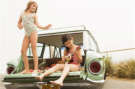 Girl dancing on car boot, another girl playing guitar Stock Photo - Premium Royalty-Free, Code: 6114-06600958