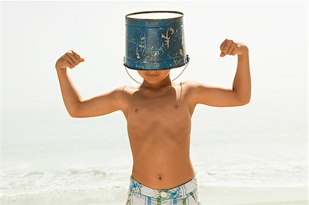 Boy with bucket on head, flexing muscles Stock Photo - Premium Royalty-Free, Code: 6114-06600967