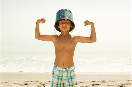 Boy with bucket on head, flexing muscles Stock Photo - Premium Royalty-Free, Code: 6114-06600966