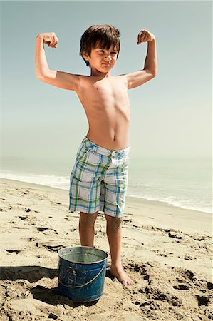Boy standing on beach flexing muscles Stock Photo - Premium Royalty-Free, Code: 6114-06600969