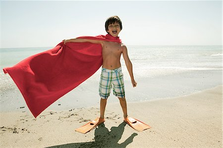 Boy wearing flippers and red cape on beach Stock Photo - Premium Royalty-Free, Code: 6114-06600973