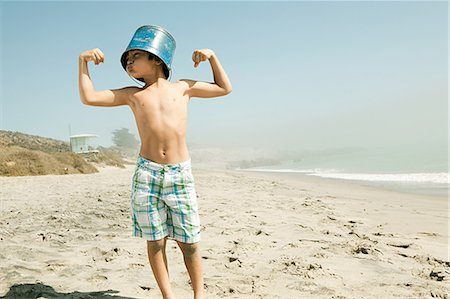 Boy with bucket on head, flexing muscles Stock Photo - Premium Royalty-Free, Code: 6114-06600970