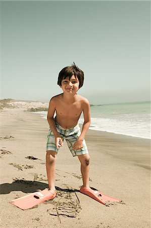 Boy standing on beach wearing swimming flippers Stock Photo - Premium Royalty-Free, Code: 6114-06600971
