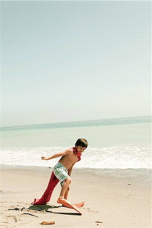 Boy wearing flippers and red cape on beach Stock Photo - Premium Royalty-Free, Code: 6114-06600972