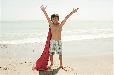 Boy wearing flippers and red cape on beach Stock Photo - Premium Royalty-Free, Code: 6114-06600974