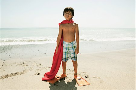 Boy wearing flippers and red cape on beach Stock Photo - Premium Royalty-Free, Code: 6114-06600975