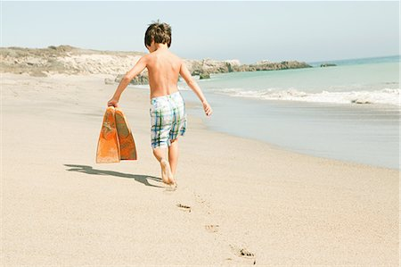 Boy on beach carrying swimming flippers Stock Photo - Premium Royalty-Free, Code: 6114-06600976