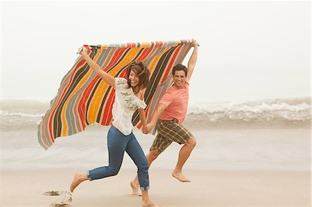 Couple running on beach under colorful blanket Stock Photo - Premium Royalty-Free, Code: 6114-06600914