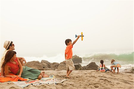 Family on beach, boy playing with toy plane Stock Photo - Premium Royalty-Free, Code: 6114-06600924