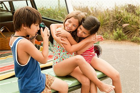 Three children sitting on back of estate car taking photographs Stock Photo - Premium Royalty-Free, Code: 6114-06600939