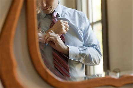 Man adjusting cuffs in mirror Stock Photo - Premium Royalty-Free, Code: 6114-06601049