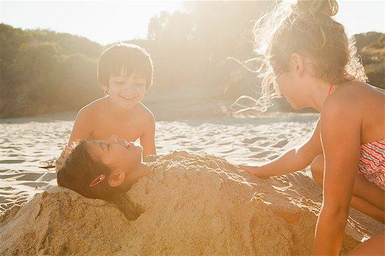 Children burying girl in sand Stock Photo - Premium Royalty-Free, Image code: 6114-06601011