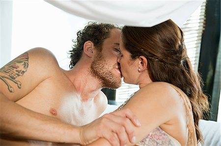 romantic couple bed - Mid adult couple kissing on vacation Stock Photo - Premium Royalty-Free, Code: 6114-06601187