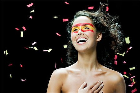 falling - Woman with Spanish flag painted on face, hand on chest and ticker tape Stock Photo - Premium Royalty-Free, Code: 6114-06601391