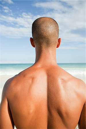 shirtless men - Topless man at beach, rear view Stock Photo - Premium Royalty-Free, Code: 6114-06601306