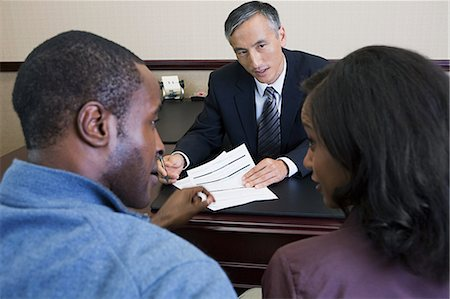 Couple talking to bank manager Stock Photo - Premium Royalty-Free, Code: 6114-06601502