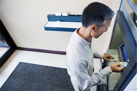 Man using cash machine Stock Photo - Premium Royalty-Free, Code: 6114-06601504