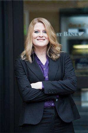 Bank teller outside bank, portrait Stock Photo - Premium Royalty-Free, Code: 6114-06601513