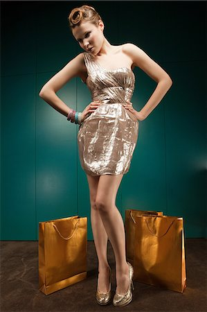 sexi women full body - Young woman wearing gold dress with shopping bags, portrait Stock Photo - Premium Royalty-Free, Code: 6114-06601767