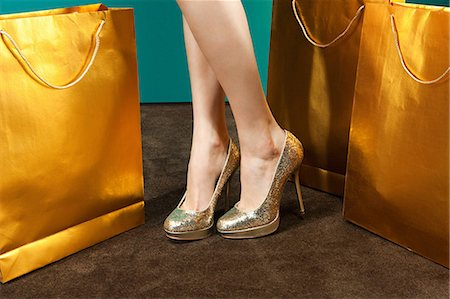 female feet close up - Young woman wearing gold stilettos with shopping bags Stock Photo - Premium Royalty-Free, Code: 6114-06601766