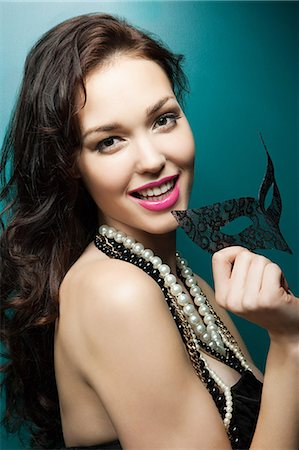 Young woman holding masquerade mask, portrait Stock Photo - Premium Royalty-Free, Code: 6114-06601787