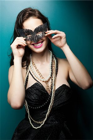 Young woman wearing masquerade mask, portrait Stock Photo - Premium Royalty-Free, Code: 6114-06601789