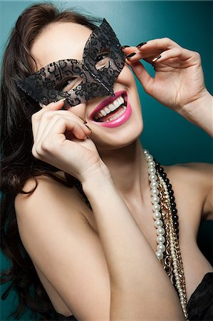 Young woman wearing masquerade mask, portrait Stock Photo - Premium Royalty-Free, Code: 6114-06601790