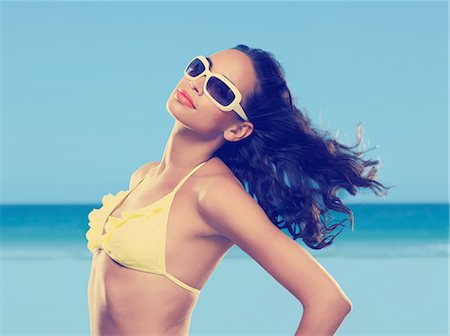 Young woman wearing yellow bikini and sunglasses Stock Photo - Premium Royalty-Free, Code: 6114-06601872