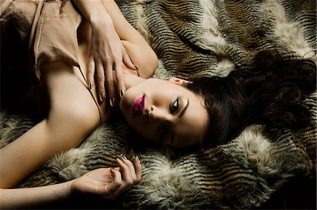 fur - Young woman lying on blanket, portrait Stock Photo - Premium Royalty-Free, Code: 6114-06601803