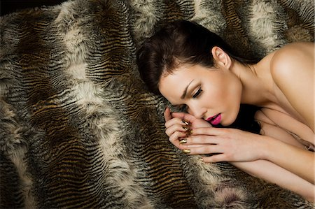 furry - Young woman lying on blanket, portrait Stock Photo - Premium Royalty-Free, Code: 6114-06601802
