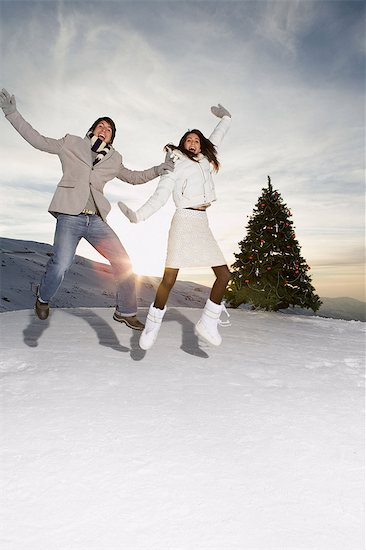 Couple jumping in the snow Stock Photo - Premium Royalty-Free, Image code: 6114-06603312