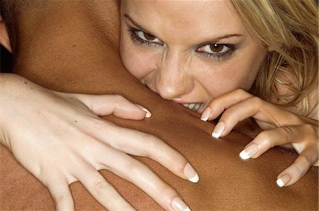 Woman biting mans shoulder Stock Photo - Premium Royalty-Free, Code: 6114-06607317