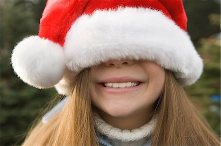 Girl with santa hat covering eyes Stock Photo - Premium Royalty-Free, Code: 6114-06608307