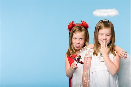 Twin girls dressed as an angel and devil Stock Photo - Premium Royalty-Free, Code: 6114-06608983